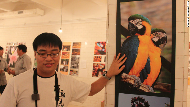 "Peter Yim, who is partially blind, shows a photo he took on Hong Kong's Lamma Island, which was part of the ""Luminance Touched"" exhibition in early November 2012."