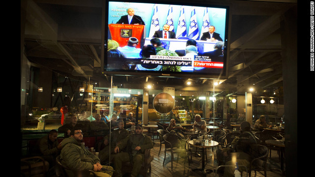 Israeli soldiers sit in a restaurant at the Yad Mordechay Junction as they watch Israeli Prime Minister Benjamin Netanyahu deliver a statement on live television from Jerusalem.
