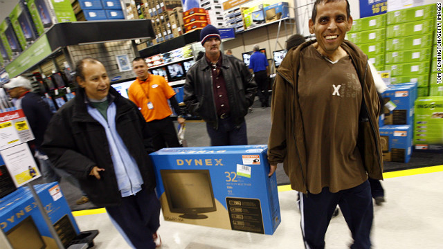 Customers in a Fort Worth, Texas, Best Buy gleefully carry off their Black Friday flatscreen TV score in 2009.