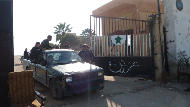 Syrian rebel fighters drive through the gate of Syrian Government Army Base 46 after its capture, near Aleppo on Wednesday. Defected Gen. Mohammed Ahmed al-Faj, who commanded the assault, hailed the capture of the base as &quot;one of our biggest victories since the start of the revolution&quot; against President Bashar al-Assad.