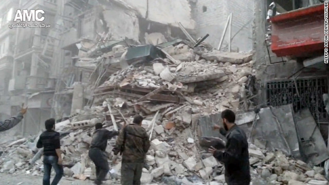 Civilians gaze at the ruins of a hospital reportedly struck Wednesday by Syrian government forces in the city of Aleppo.