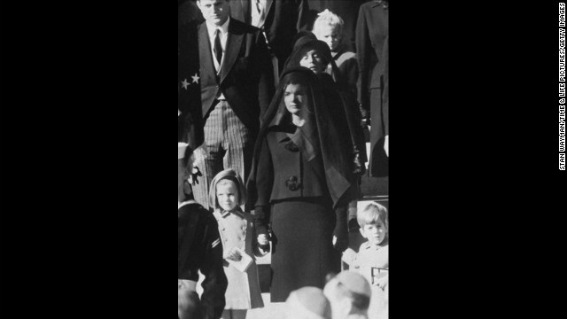 On November 22, 1963, President John F. Kennedy was assassinated while in a presidential motorcade in Dallas. Pictured, Kennedy's widow, Jacqueline Kennedy, children, Caroline and John, and mother, Rose Kennedy, behind, wait outside St. Matthew's Cathedral for the procession to the cemetery during his funeral on November 25.