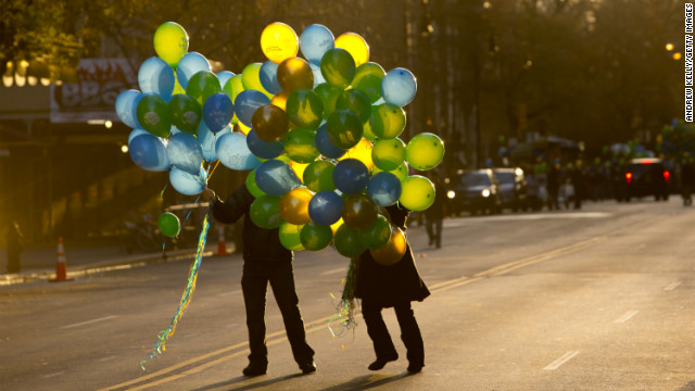 People hand out balloons on 72nd Street before the parade.