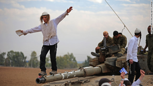 A Hasidic Jewish boy dances on the barrel of a tank Thursday as he and others celebrate the Israeli soldiers.