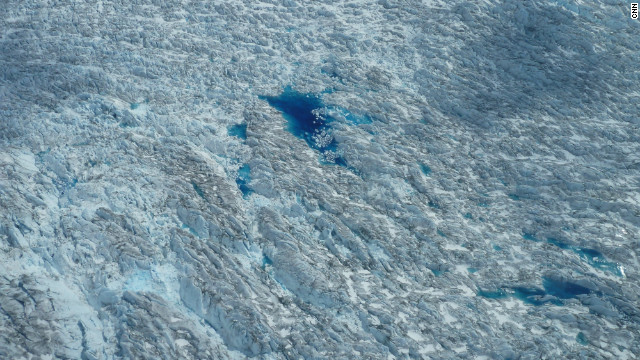 Meltwater ponds below indicate surface melt during the arctic summer. 