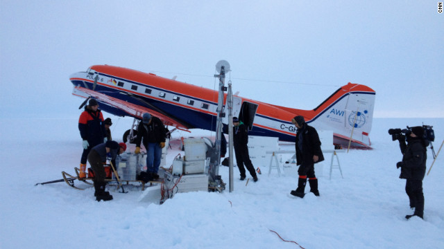 The crew at an ice core drill site after landing safely on the ice. The drilling has to be performed at night because the surface is so slushy from ice melt during daylight that the plane would sink in and get stuck.