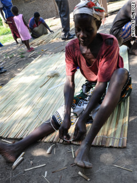A Kenyan woman weaves a ceiling mat, an effective and environmentally sound tool used to prevent entry of malaria-transmitting mosquitoes into rural homes.
