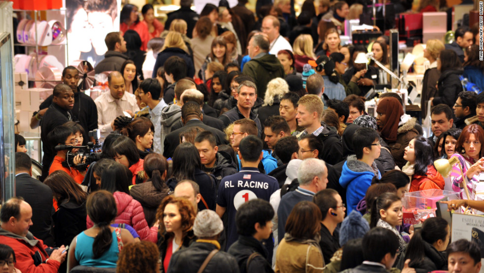 Shoppers crowd a Macy's in New York for the store's Black Friday sale, which started at midnight Friday, November 23. Some stores opened even earlier, cutting into the Thanksgiving celebrations and indicating that even this cherished American family holiday is falling prey to the forces of commerce.