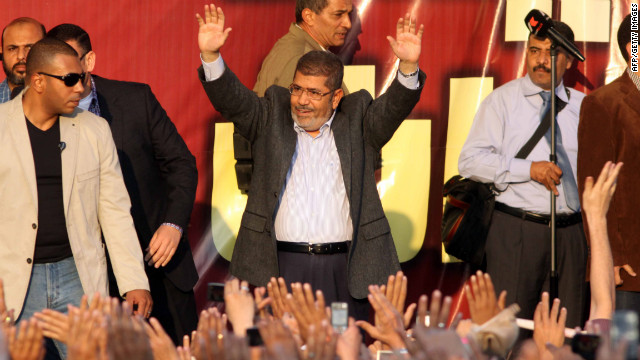 Egyptian President Mohamed Morsy waves to supporters in front of the presidential palace in Cairo on Friday, November 23. Thousands of ecstatic supporters gathered outside the presidential palace to defend their leader against accusations from rival protesters that he has become a dictator.