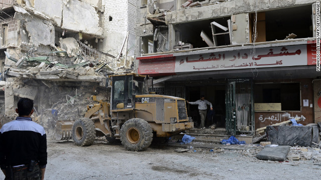 Syrian rebels and bystanders watch as a bulldozer removes debris from outside the Dar Al-Shifa hospital in Aleppo on Thursday, November 22.