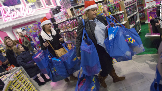 Shoppers leave the Toys R Us holiday sale with bags of goodies.