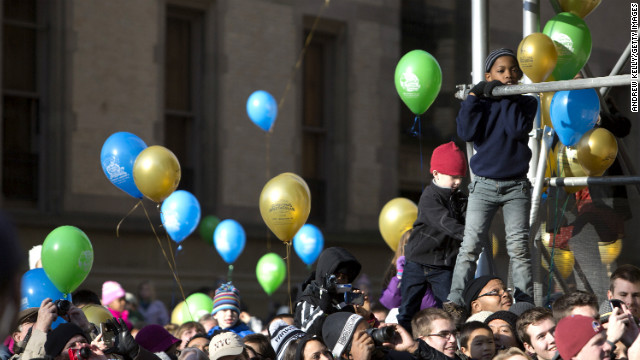 People climb for a better position to watch the Macy's Thanksgiving Day Parade.