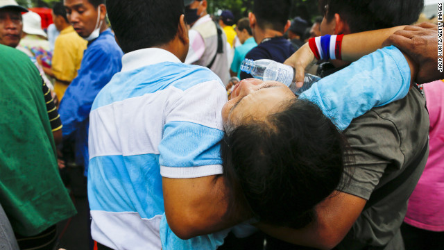 Protesters carry one of their own after she was overcome by tear gas on Saturday. 