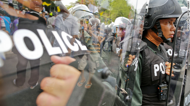 Riot police shield themselves from protesters on Saturday.
