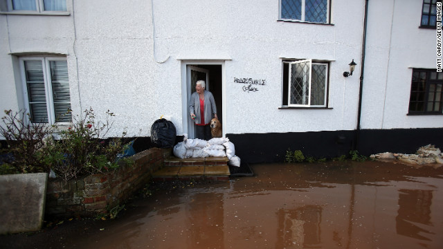 Anne Bartlett and her dog Henry look out from their flooded property in Somerset, England, on Sunday.