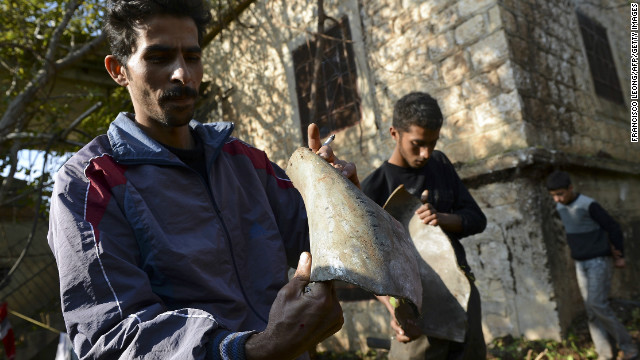Syrian men display the remains of a bomb Monday in the village of Atimah, near the Turkish border, in Syria's Idlib province.