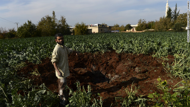 A man stands next to a crater in the village of Atme after a Syrian warplane launched an attack against a rebel command center near the border with Turkey on Monday.