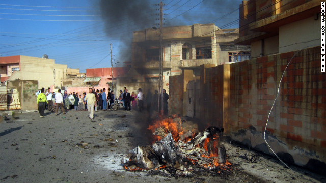 The remains of one of three car bombs burns in the northern Iraqi city of Kirkuk on Tuesday.