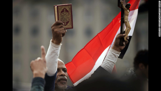 An Egyptian protester holds up a Quran and a figure of Christ on the cross during Tuesday's demonstration.