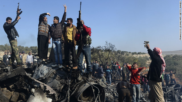 Syrian rebels celebrate on top of the remains of a Syrian government fighter jet that was shot down at Daret Ezza, on the border between the provinces of Idlib and Aleppo, on Wednesday.