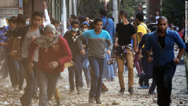 Protesters run from Egyptian riot police during clashes near Cairo's Tahrir Square on Wednesday, November 28.