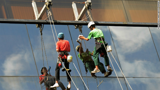 Workers clean windows of a building in Manila on November 28, 2012.