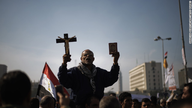 A man holds a copy of the Quran and a cross in Tahrir Square on November 30.
