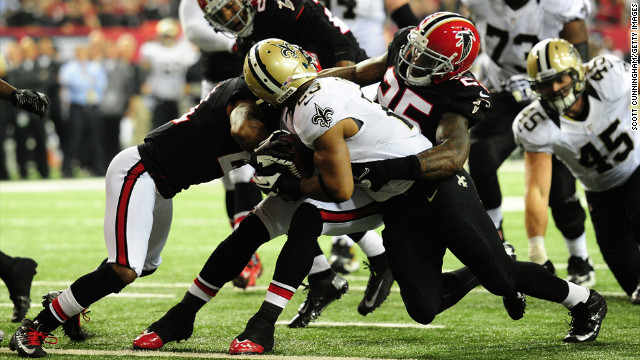 Pierre Thomas of the New Orleans Saints gets a face mask tackle by William Moore of the Atlanta Falcons during a run on Thursday, November 29, 2012, at the Georgia Dome in Atlanta.