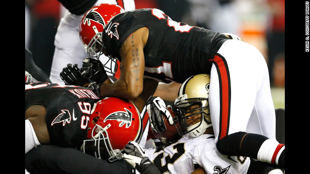 Pierre Thomas of the New Orleans Saints is tackled by Sean Weatherspoon and Chris Owens of the Atlanta Falcons on Thursday.
