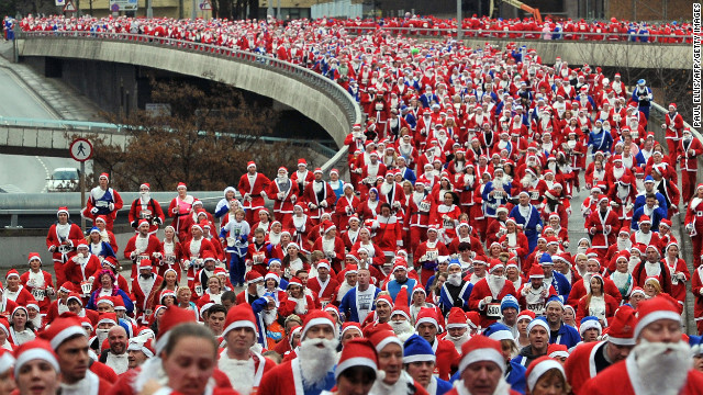 Runners dressed in Father Christmas costumes take part in the annual 5-kilometer Santa Dash in Liverpool, England, on Sunday, December 2. Many runners who refuse to run in red, the color of their football rivals Liverpool FC, wear blue to support the football team Everton FC<!-- -->.</br><!-- --> </br>
