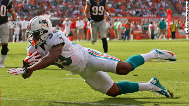 Daniel Thomas of the Miami Dolphins falls during the game against the New England Patriots on Sunday.