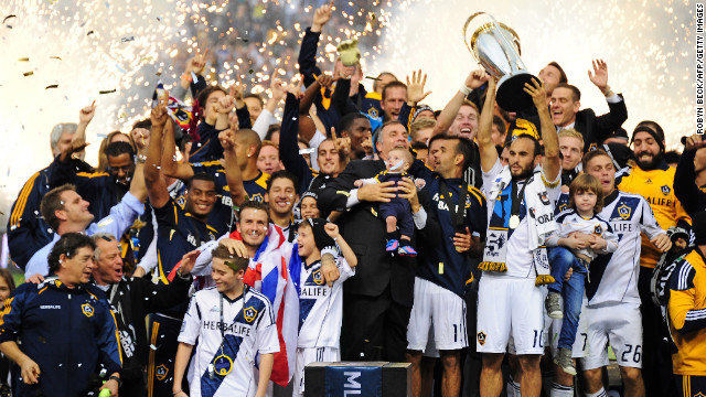Galaxy captain Landon Donovan holds up the MLS Trophy as David Beckham, lower left, and other teammates celebrate their win.