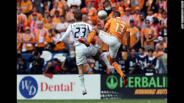 Beckham and Houston's Ricardo Clark go for a header in the first half.