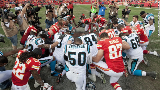 Players from the Kansas City Chiefs and Carolina Panthers gather at midfield Sunday for a prayer after the Chiefs' 27-21 win.