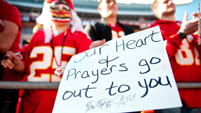 A young fan holds a condolences sign for the Kansas City Chiefs prior to the team's game against the Carolina Panthers.