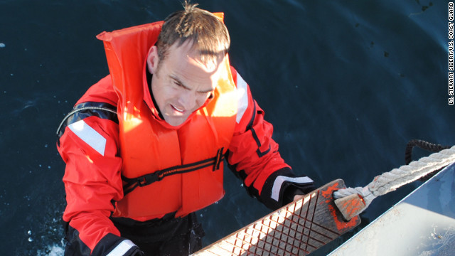 Coast Guard Chief Petty Officer Terrell Horne, stationed on the Cutter Halibut, climbs into the ship after conducting water survival training in this undated photograph.
