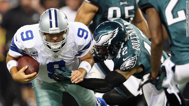 Cowboys quarterback Tony Romo runs the ball for a first down Sunday as Kurt Coleman of the Eagles makes the tackle.