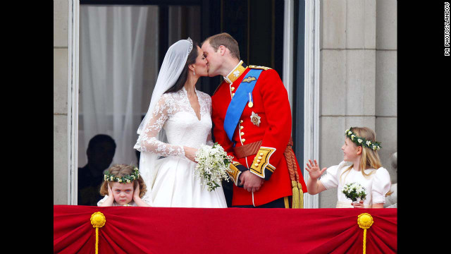 Prince William and Kate kiss on the balcony of Buckingham Palace in London after their wedding at Westminster Abbey on April 29, 2011. Two young bridesmaids, Grace Van Cutsem, left, and Margarita Ar