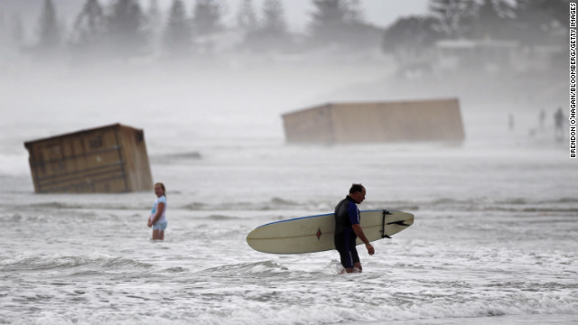 January 10: A surfer walks past cargo containers washed ashore from the stricken container ship Rena at Waihi Beach in New Zealand. The ship was stranded on a reef for more than three months before breaking up and sinking in rough seas, littering beaches with cargo and debris.