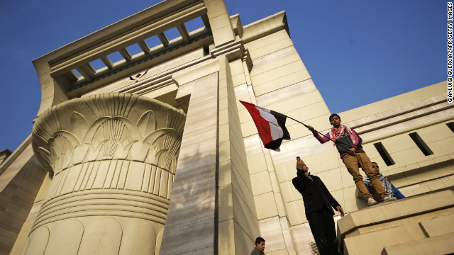 A Morsy supporter waves a flag outside the Supreme Constitutional Court as hundreds of supporters of the president protest on Sunday, December 2, in Cairo, forcing judges to postpone a hearing on a constitutional panel at the heart of a deepening political crisis.