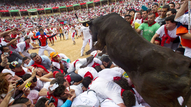 July 8: A wild bull hurdles over people blocking the animal's way into the bullring at the close of the second bull run during the Fiesta de San Fermin in Pamplona, Spain. The festival attracts thousands of people who attempt to outrun the bulls through the narrow streets of the old city.