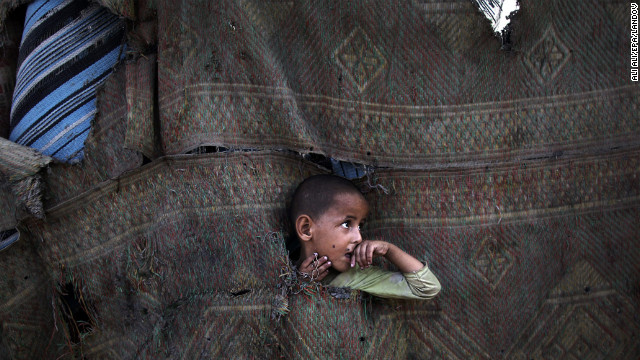 July 22: A Palestinian refugee plays in between makeshift tents in the Al-Zaiton neighborhood before breaking fast on the third day of the holy month of Ramadan in Gaza. During Ramadan, Muslims fast from dawn to dusk. 