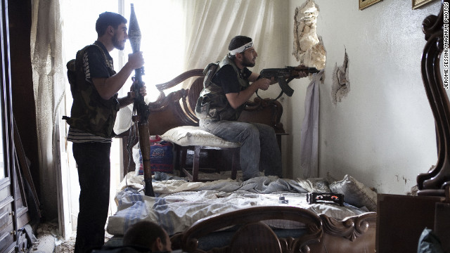 October 19: Free Syrian Army fighters watch a regime army position through a hole in a wall in Aleppo, Syria's most populous city..