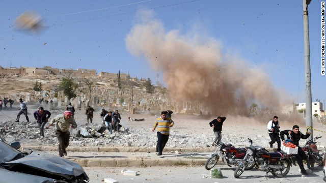 November 4: Syrians take cover as a second bomb explodes during a rescue attempt in a nearby building that was hit during an air raid by government forces in the northern city of Al-Bab.