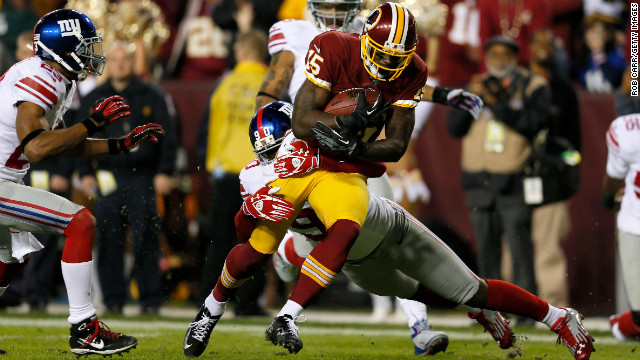 Josh Morgan of the Washington Redskins runs the ball as he is hit by Jason Pierre-Paul of the New York Giants before scoring a touchdown after recovering a fumble on Monday, December 3, at FedExField in Landover, Maryland. Check out the action from Week 13 of the NFL, and look back at the best photos from Week 12.