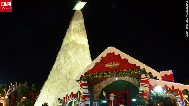 In the Philippines, Christmas trees come in all shapes and sizes -- this one in iReporter Miaflor Tatlonghari's image is at least 30ft tall and towers over Santa Claus's house in Santa Rosa city.