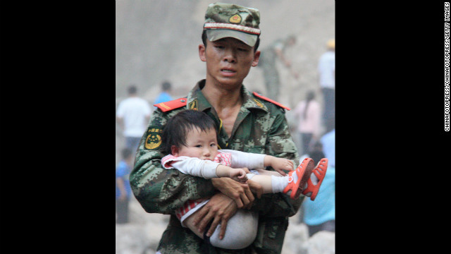 September 9: A rescue worker carries a child in Yiliang County, China. At least 80 people were killed and more than 800 others were injured after two earthquakes jolted southwest China.
