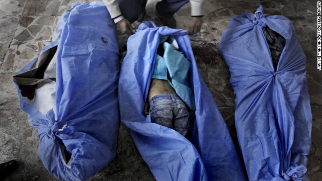 The bodies of three children reportedly killed in a mortar shell attack are laid out for relatives to identify at a makeshift hospital in Aleppo on December 2.