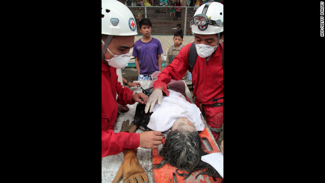 Red Cross volunteers assist a rescued child in New Bataan on December 5.