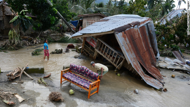 Residents clean their sofa next to their damaged house in New Bataan township on December 5.